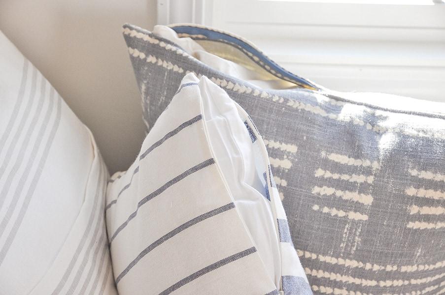 cost of DIY pillows, stripe fabric, on window seat, ikea dish towel, tablecloth, pottery barn shobori dot napkin