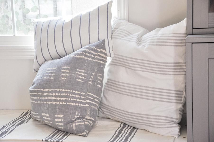 decorative throw pillows in stripe fabric, on window seat, ikea dish towel, tablecloth, pottery barn shobori dot napkin