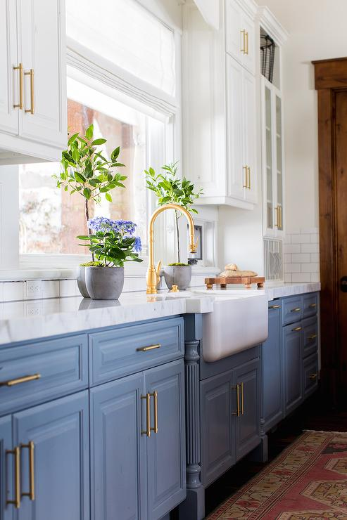 blue lower cabinet, white upper cabinet, brass fixtures and hardware in a modern farmhouse kitchen