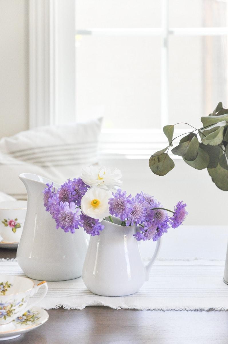 white ceramic pitcher, pincushion flowers, farmhouse dining table